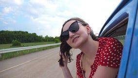 Muchacha feliz en las gafas de sol que se inclinan fuera de la ventanilla del coche del vintage y que disfrutan de viaje Mujer jo metrajes