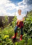 Muchacha feliz en los gumboots rojos que trabajan en el jardín del patio trasero Fotos de archivo libres de regalías
