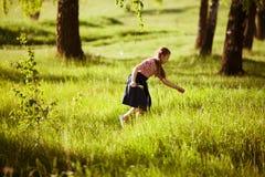 Muchacha feliz en los rasgones de la hierba de prado Fotos de archivo