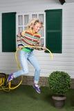 Muchacha feliz en salto con el tubo amarillo Fotos de archivo