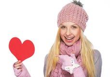Muchacha feliz en sombrero del invierno que señala en postcardsh en forma de corazón Fotos de archivo libres de regalías