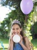 Muchacha feliz en Tiara Blowing Balloons Outdoors Imágenes de archivo libres de regalías