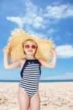 Muchacha feliz en traje de baño rayado y sombrero de paja grande en la playa blanca Fotos de archivo libres de regalías