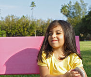 Muchacha feliz en un banco Imagen de archivo libre de regalías