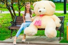 muchacha feliz en un banco con su oso de peluche preferido Imagenes de archivo