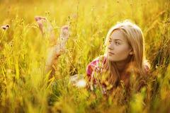 Muchacha feliz en un campo de la hierba y de las flores Fotografía de archivo