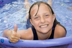 Muchacha feliz en un donante de la piscina pulgares para arriba. Fotografía de archivo