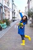 Muchacha feliz en un impermeable azul en la calle de la ciudad vieja En las manos de una botella de vino rojo y de dos vidrios fotografía de archivo libre de regalías