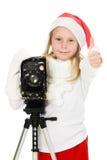 Muchacha feliz en un traje de la Navidad con la cámara vieja Imágenes de archivo libres de regalías