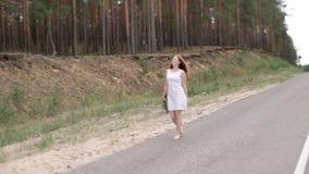 Muchacha feliz en un vestido blanco con un ramo en sus manos que camina descalzo a lo largo del camino almacen de metraje de vídeo