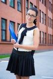 Muchacha feliz en uniforme escolar con la mochila en campus Imagen de archivo