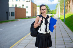 Muchacha feliz en uniforme escolar con la mochila que se coloca en la calle Fotos de archivo