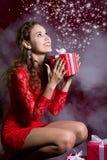 Muchacha feliz en vestido rojo con la caja de regalo Imagen de archivo