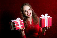 Muchacha feliz en vidrios con dos regalos Fotografía de archivo