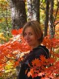 Muchacha feliz entre las hojas de arce Fotografía de archivo