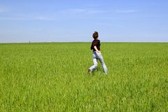 Muchacha feliz funcionada con en el prado Fotos de archivo libres de regalías