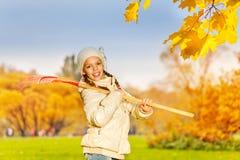 Muchacha feliz hermosa con el rastrillo en su hombro Imagenes de archivo