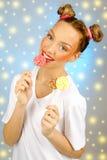 Muchacha feliz hermosa con las pecas que sostienen y que comen la piruleta del caramelo de los dulces con la expresión facial Imagen de archivo