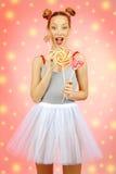 Muchacha feliz hermosa con las pecas que sostienen y que comen la piruleta del caramelo de los dulces con la expresión facial Foto de archivo