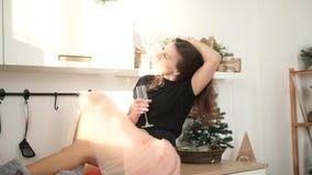 Muchacha feliz hermosa con un vidrio de champán Día de fiesta, Año Nuevo, cocina almacen de metraje de vídeo