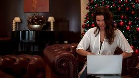 Muchacha feliz hermosa en sentarse en el sofá de lujo con el ordenador portátil en el árbol de navidad hermoso de oro con las luc imagenes de archivo