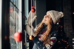Muchacha feliz hermosa en sombrero y manoplas con los juguetes de la Navidad Fotos de archivo libres de regalías