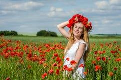 Muchacha feliz hermosa joven con el pelo largo en un vestido blanco en el campo de la amapola con una guirnalda en su cabeza Fotografía de archivo libre de regalías