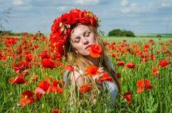 Muchacha feliz hermosa joven con el pelo largo en un vestido blanco en el campo de la amapola con una guirnalda en su cabeza Imágenes de archivo libres de regalías