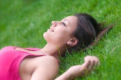 Muchacha feliz hermosa que miente en la hierba verde Imagen de archivo libre de regalías