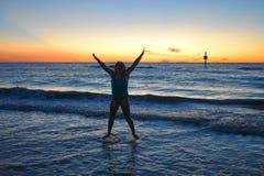 Muchacha feliz hermosa que salta en el océano azul en la playa de Clearwater imagen de archivo libre de regalías