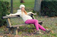 Muchacha feliz hermosa que se sienta en parque del otoño Fotografía de archivo