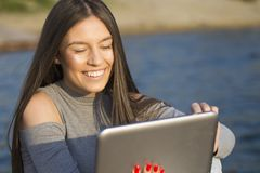 Muchacha feliz hermosa que se sienta por el mar y la tableta del uso fotos de archivo libres de regalías