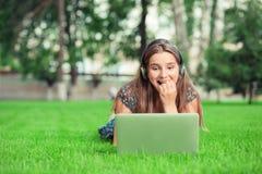 Muchacha feliz impaciente tensa mientras que ella espera una llamada de la web o una respuesta a su charla o SMS en el ordenador  foto de archivo libre de regalías