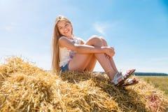Muchacha feliz joven con el pelo rubio largo que se sienta en pajares en un campo del trigo maduro Imagen de archivo libre de regalías