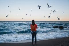 Muchacha feliz joven con las gaviotas de alimentación de la mochila anaranjada en un rato de la tarde de la playa Fotografía de archivo