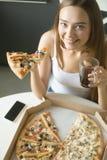 Muchacha feliz joven con una rebanada de pizza Imagenes de archivo