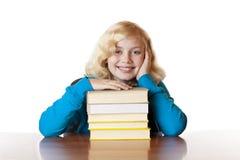 Muchacha feliz joven de la escuela que se sienta con los libros en el escritorio Fotografía de archivo