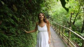 Muchacha feliz joven de la raza mixta en el vestido blanco que camina en bosque de la selva, mirando alrededor y tocando con las  almacen de video