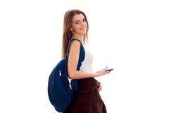 Muchacha feliz joven del estudiante con la presentación azul de la mochila aislada en el fondo blanco en estudio Fotografía de archivo