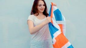 Muchacha feliz joven del patriota que sostiene la Gran Bretaña, bandera de Union Jack almacen de video