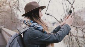Muchacha feliz joven del viajero con la mochila que toma la foto del smartphone, caminando a lo largo de la orilla del río debajo almacen de video
