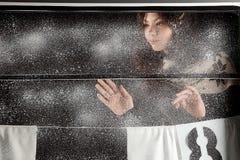 Muchacha feliz joven detrás de la ventana de la nieve en fondo negro Fotografía de archivo libre de regalías
