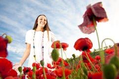 Muchacha feliz joven en amapolas Imagen de archivo libre de regalías