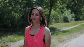Muchacha feliz joven en auriculares que camina en parque Mujer atractiva que disfruta de su paseo Muchacha que se relaja después  almacen de metraje de vídeo