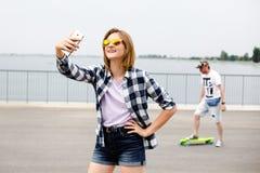 Muchacha feliz joven en el inconformista que hace el selfie en el teléfono fotos de archivo