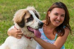 Muchacha feliz joven que abraza su perro Fotografía de archivo libre de regalías