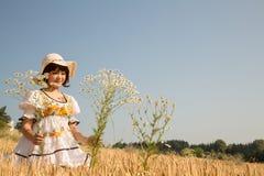 Muchacha feliz joven que camina en un campo de trigo y flores de las selecciones Imagen de archivo