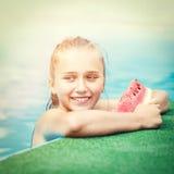 Muchacha feliz joven que come la sandía en piscina Foto de archivo