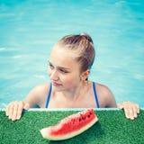 Muchacha feliz joven que come la sandía en piscina Foto de archivo libre de regalías