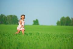 Muchacha feliz joven que corre en el campo de trigo verde Imagen de archivo libre de regalías